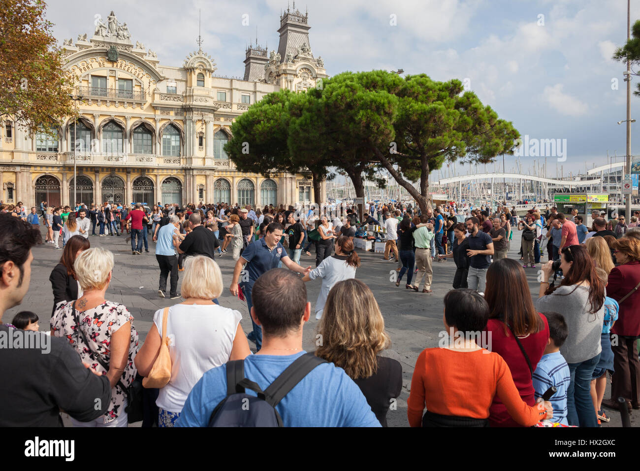 Spain, Catalonia, Barcelona, people dancing, watching and hanging out on a square in front of Port Authority Building, - Stock Image