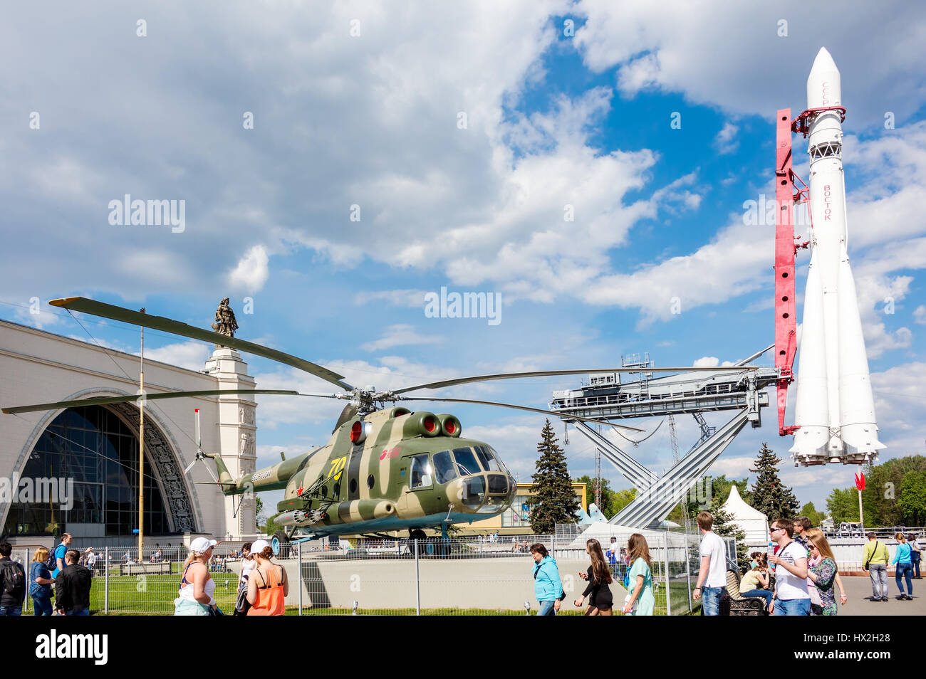 MOSCOW - MAY 8, 2016: People near the military transport helicopter Mil Mi-8T and Vostok rocket in VDNKh park. It - Stock Image