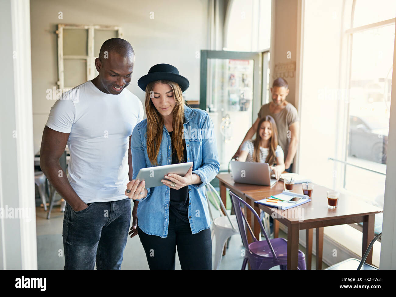 Young stylish female sharing something on tablet with male co-worker with other people on background in office. - Stock Image