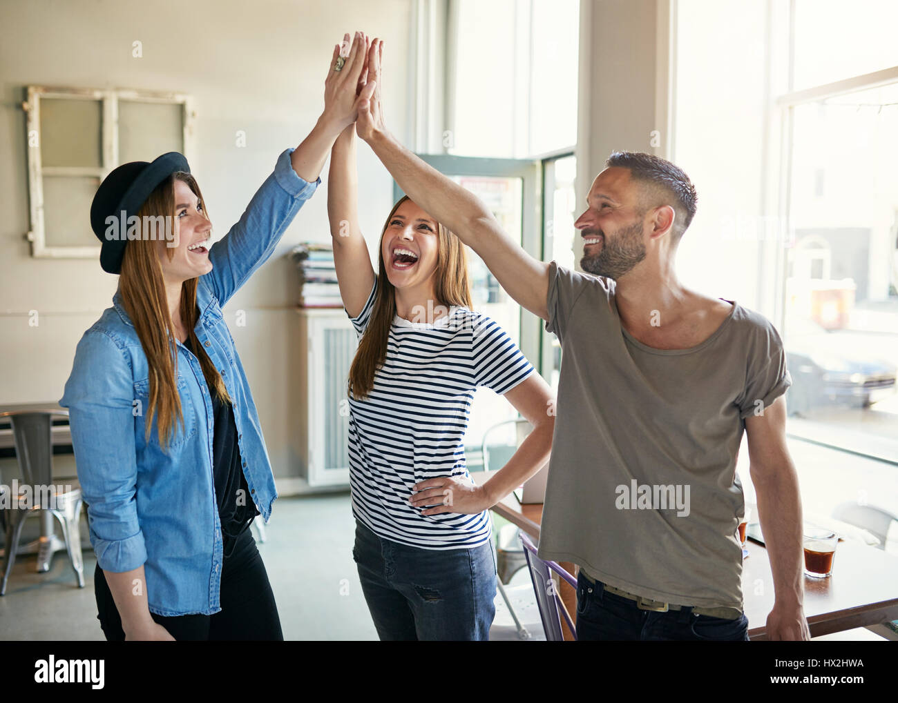 Young smiling trendy co-workers making gesture of high five in light spacious office. - Stock Image