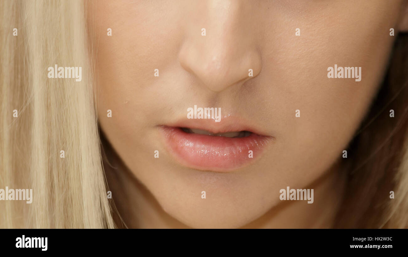 the lips of a beautiful young women saying though words waiting to hear. - Stock Image