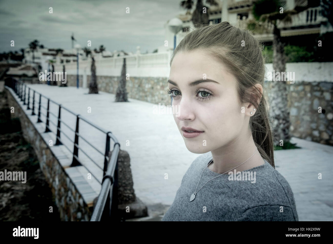 A overcast image of a teenage girl alone on a promenade by the sea. - Stock Image