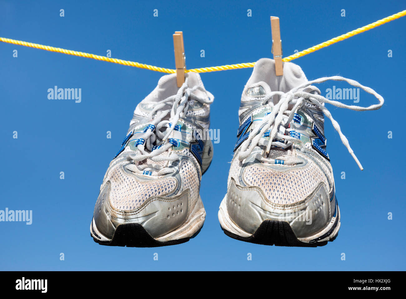 Pair of old trainers hanging on a clothes line. - Stock Image
