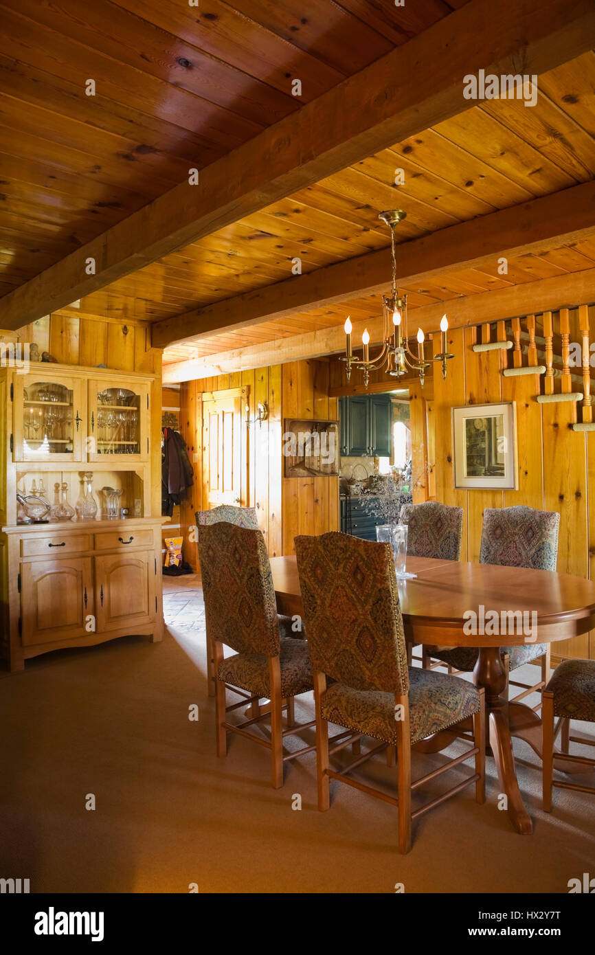 Antique table with upholstered high back chairs and buffet in dining room of 1977 log home interior - Stock Image