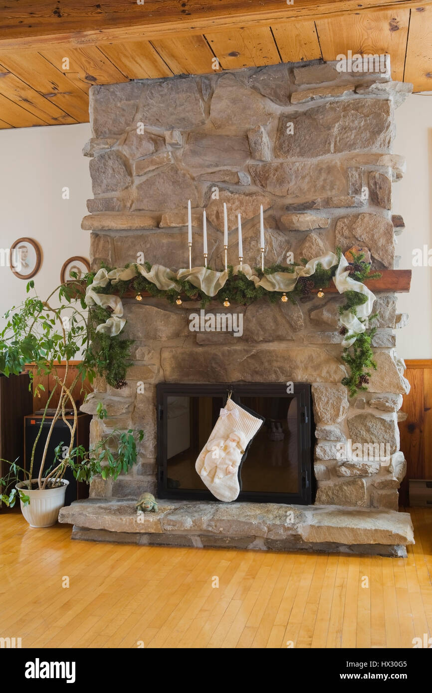 Natural stone fireplace with christmas decorations in the living room of a 1982 reconstructed old log home interior
