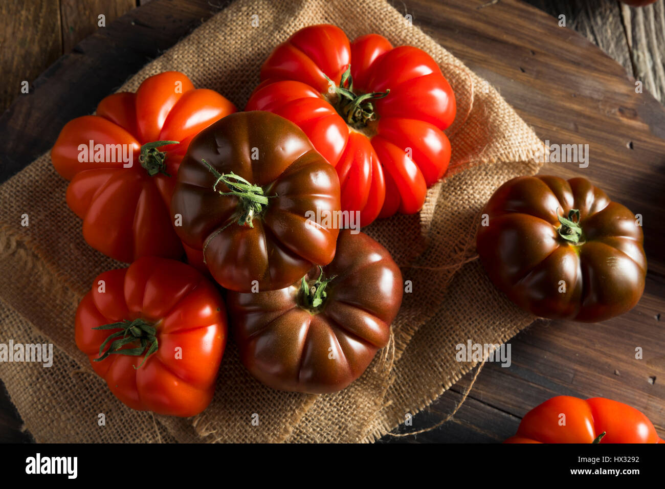 Raw Organic Red and Brown Heirloom Tomatoes Fresh of the Vine - Stock Image
