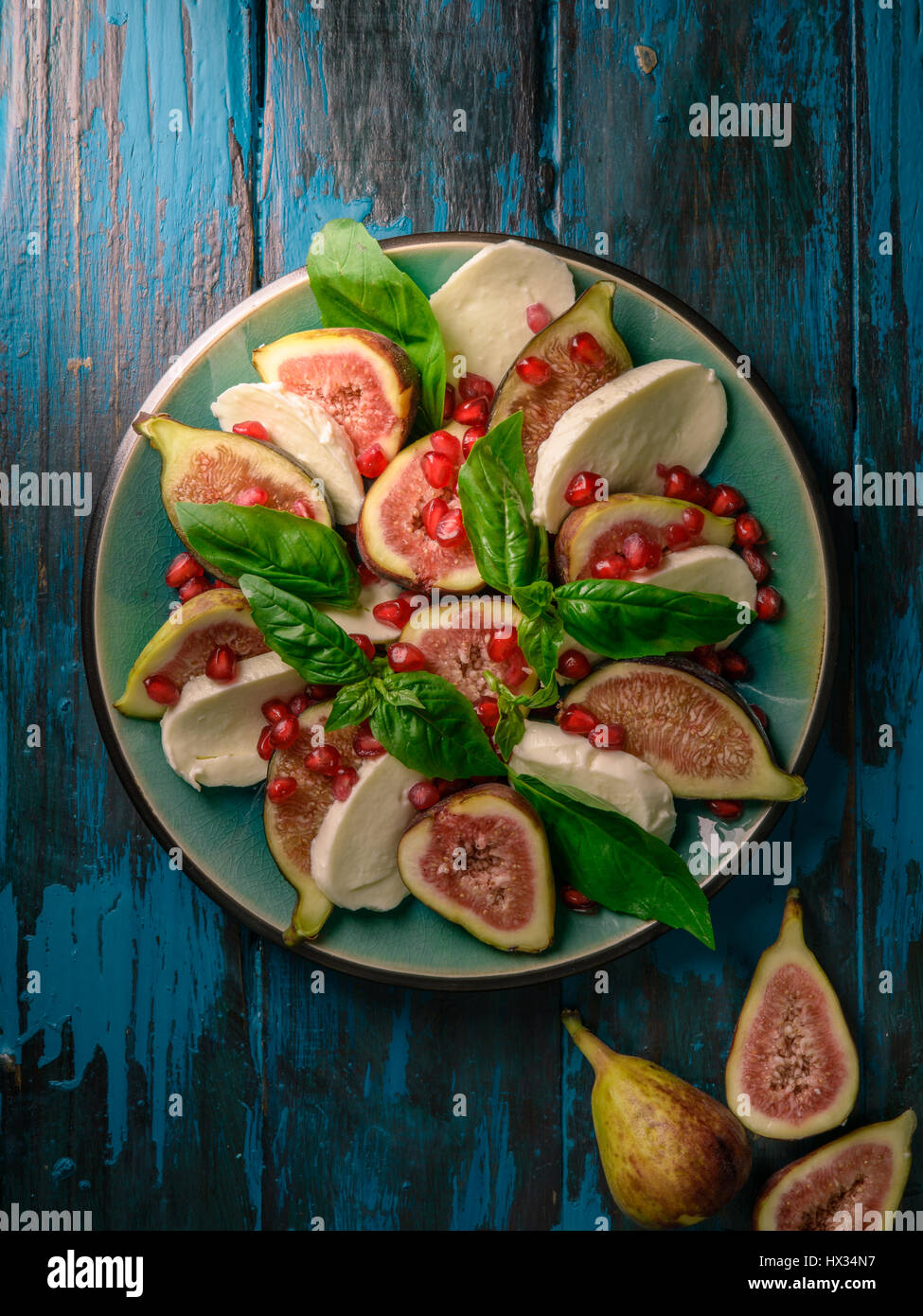 Figs with Mozzarella and Pomegranate Seeds on distressed wooden tabletop - Stock Image