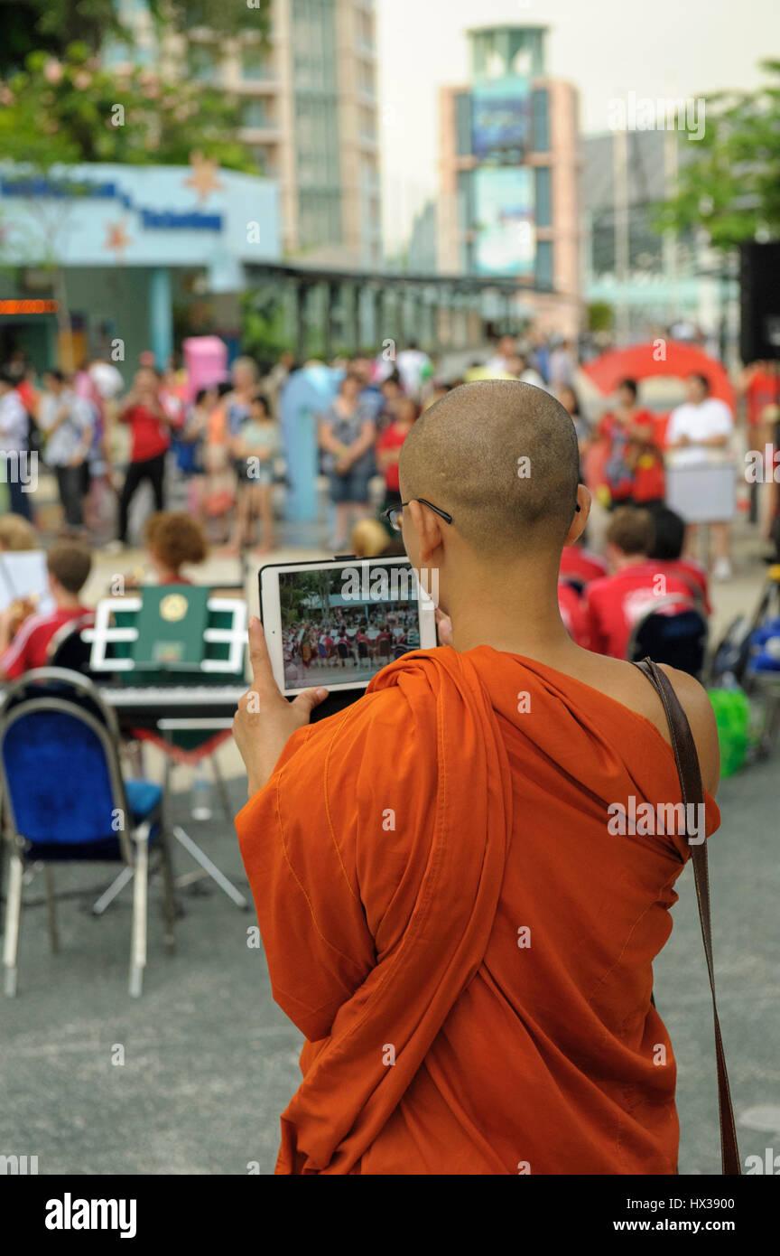 Novice Buddhist monk taking video using modern electronic tablet. - Stock Image