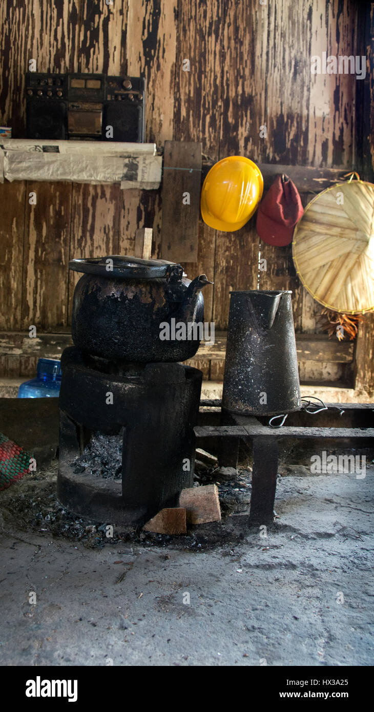 Black old kettle on sitting on small old firewood stove filled with charcoal inside wooden hut in the afternoon. - Stock Image