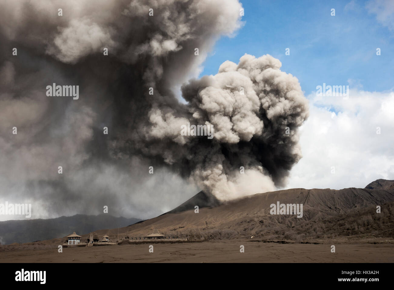 Grey smoke coming out of an active volcano filling the sky at the Tengger Semeru National Park in East Java, Indonesia. Stock Photo