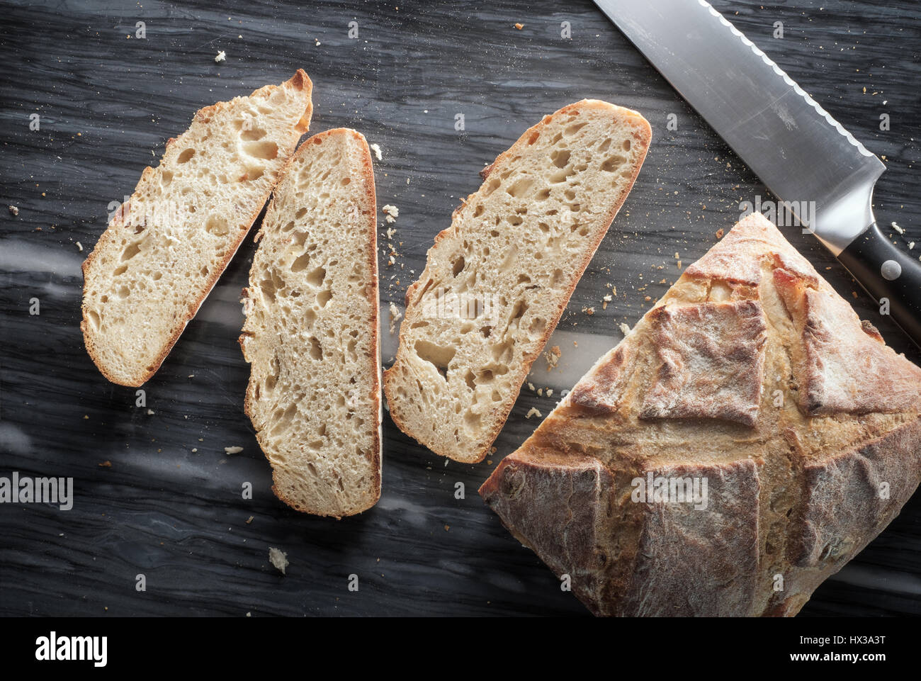 Partially-sliced artisan bread - from above - Stock Image