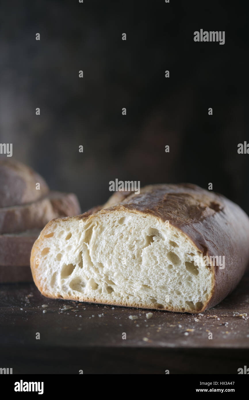 Loaf of white bread against dark background - Stock Image