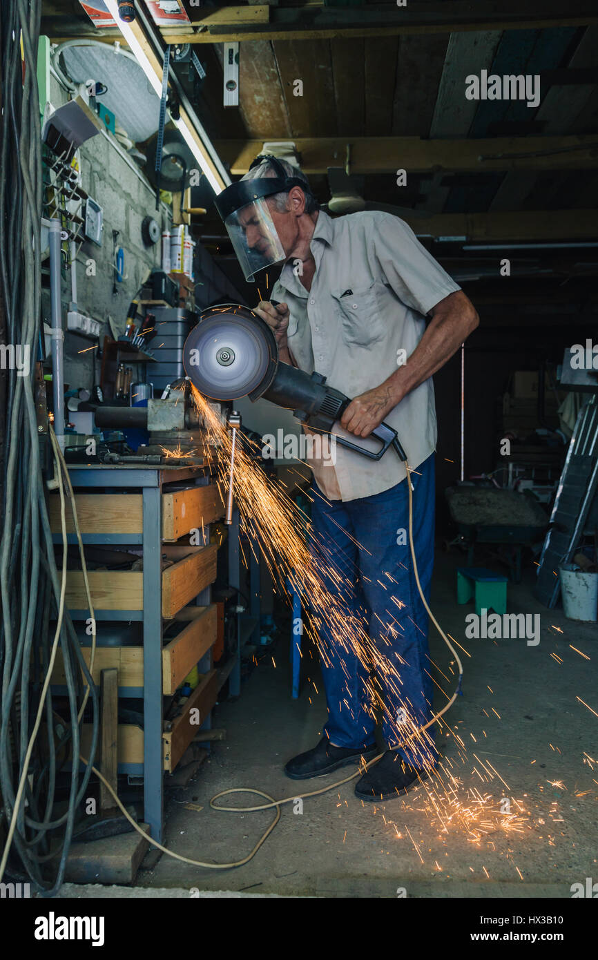 Senior man working with angle grinder - Stock Image