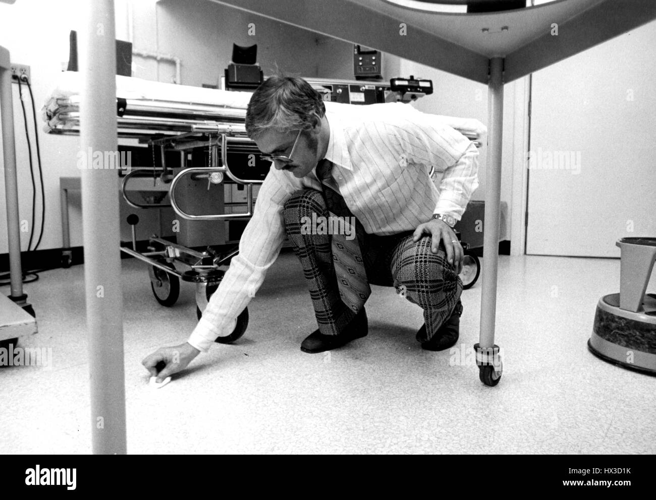 An inspector for the Atomic Energy Commission swabs the floor of a licensed hospital to test for radioactive contamination, - Stock Image