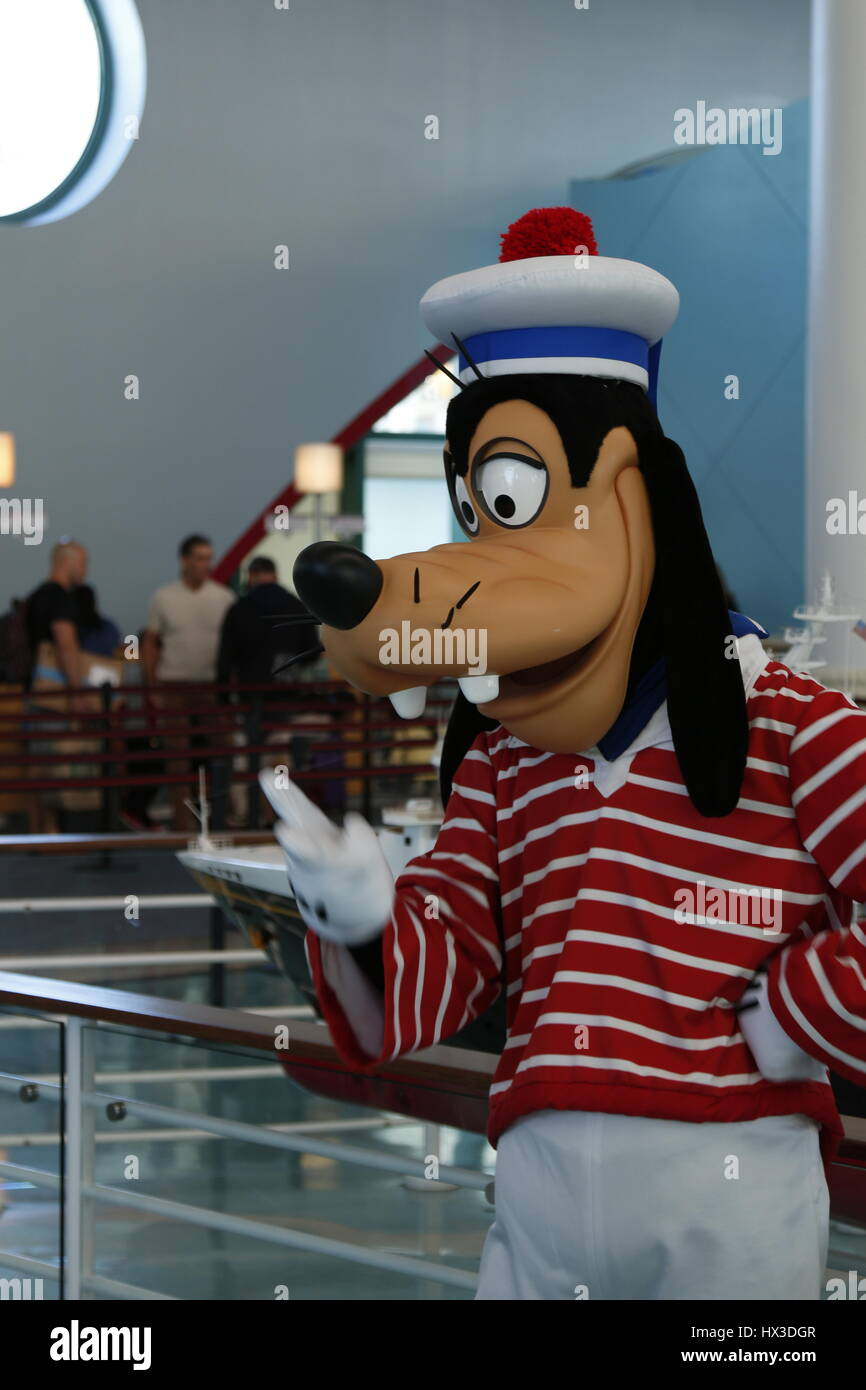 Goofy welcoming passengers aboard a Disney cruise ship. - Stock Image