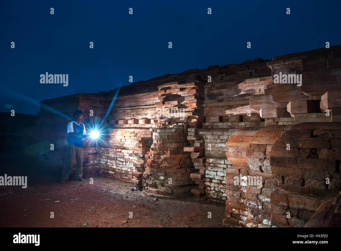 A local man using a flashlight toward the wall of Blandongan Temple during its reconstruction period in Karawang, - Stock Image