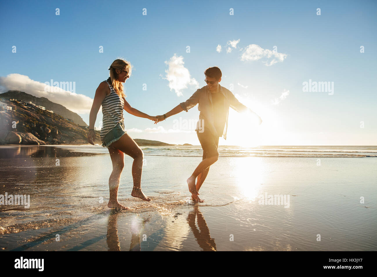 Full length shot of young couple holding hands walking on the beach and having fun. Young man and woman enjoying - Stock Image