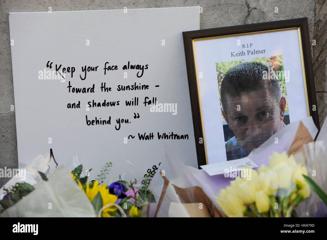 London, UK.  24 March 2017.  A portrait of slain policeman PC Keith Palmer is seen amongst the floral tributes are - Stock Image