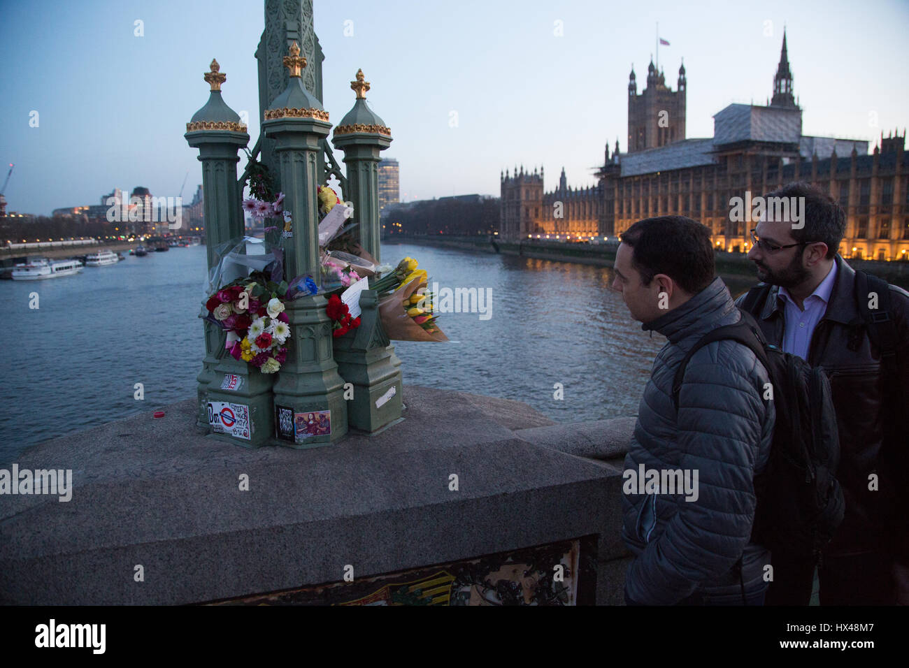 London, UK. 24th Mar, 2017. Two Men look at floral tributes on Westmister bridge folowing Wednesday's attack - Stock Image
