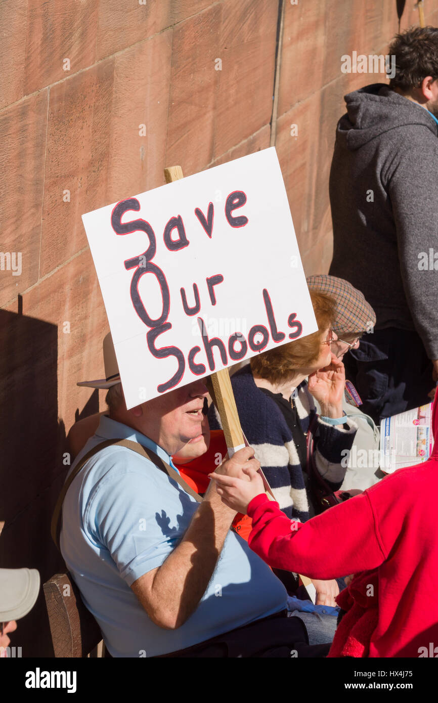 Chester, Cheshire, United Kingdom. 25th March, 2017. A elderly protestor his Save Our Schools banner during warm - Stock Image