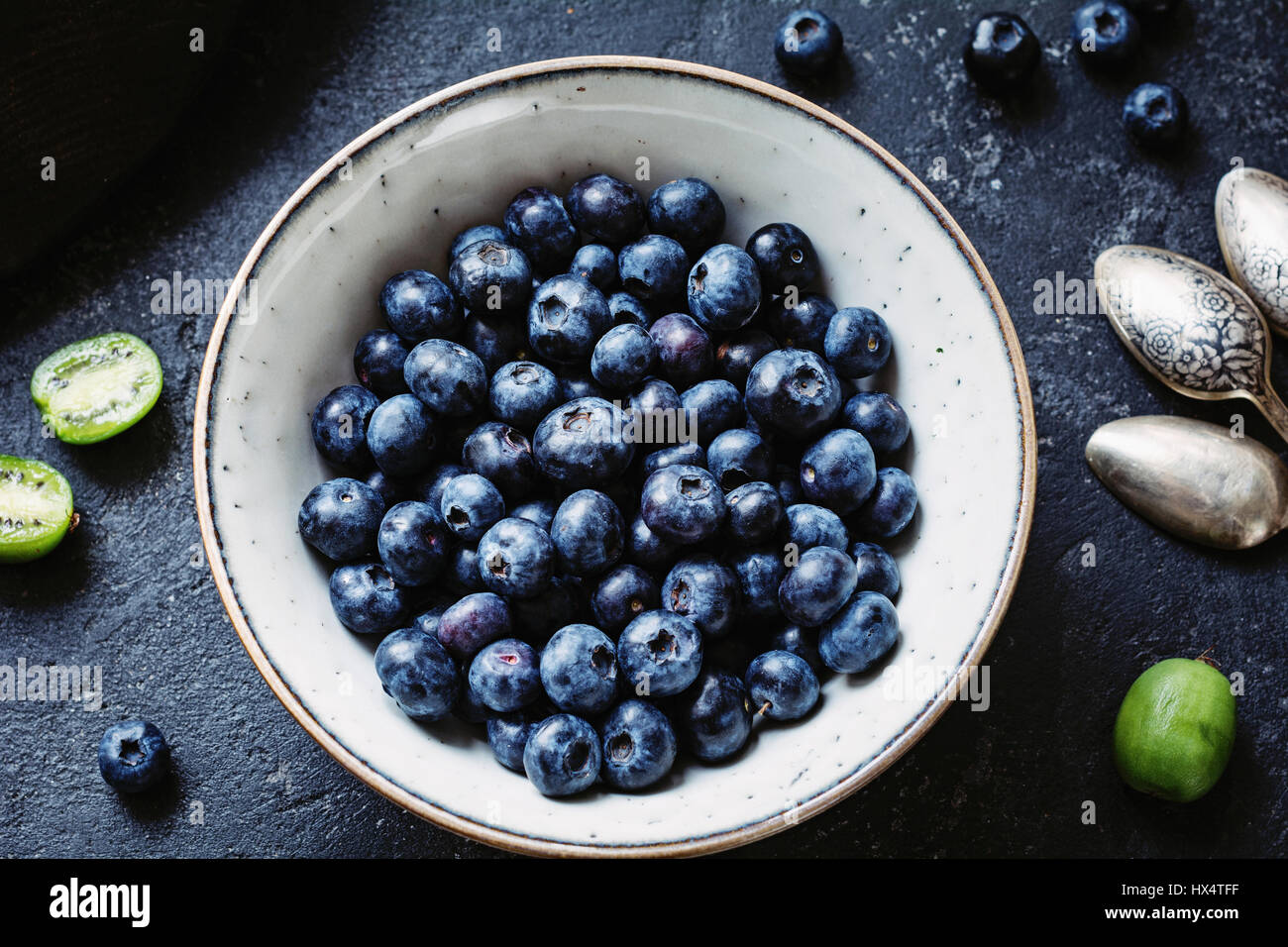 Top view of fresh blueberries in white ceramic bowl on dark stone table. Closeup - Stock Image