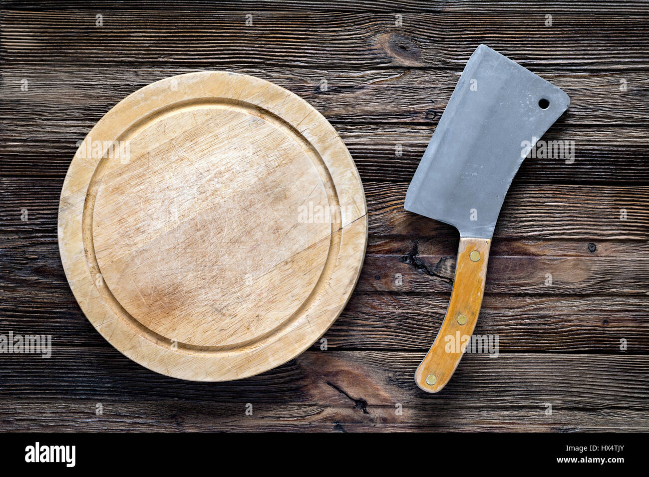 Old meat cleaver or butcher knife and round wooden chopping board. Top view with copy space - Stock Image