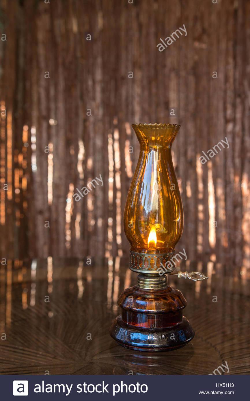 Old-fashioned kerosene lamp on brown background - Stock Image