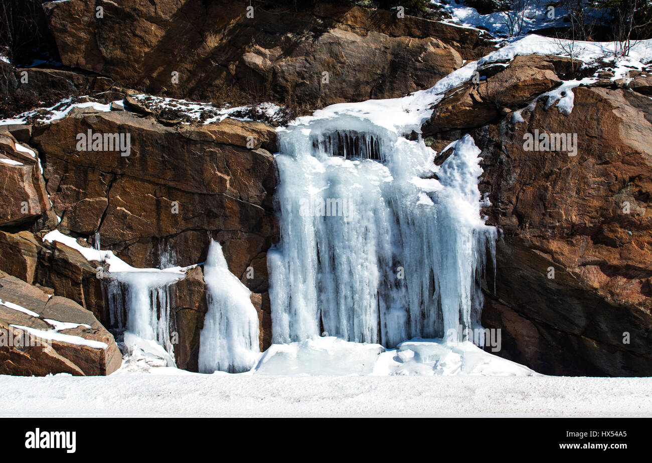 Natural stone rock face with ice from runoff - Stock Image