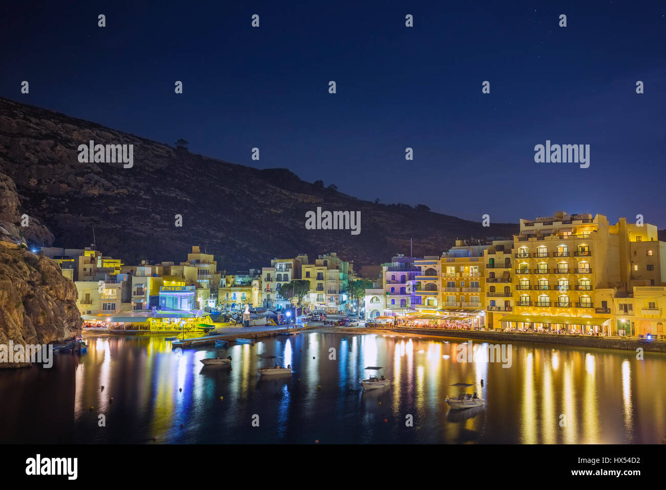 Xlendi, Gozo - Beautiful aerial view over Xlendi Bay by night with restaurants and busy night life on the Island - Stock Image