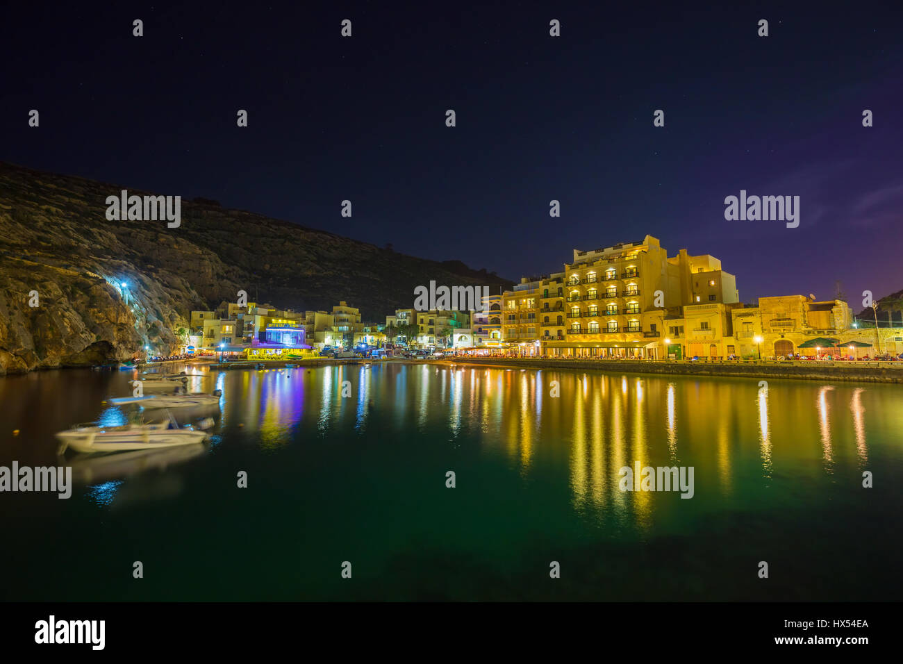 Xlendi, Gozo - Beautiful aerial view over Xlendi Bay by night with restaurants, boats and busy night life on the - Stock Image