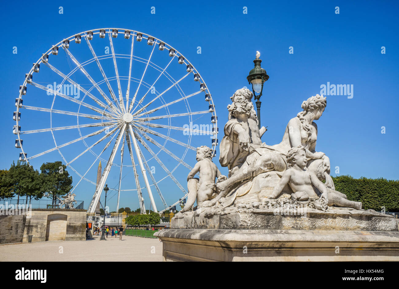 France, Paris, classic statuary at the Tuileries Gardens against the backdrop of the Grand Carousel Ferries Wheel - Stock Image
