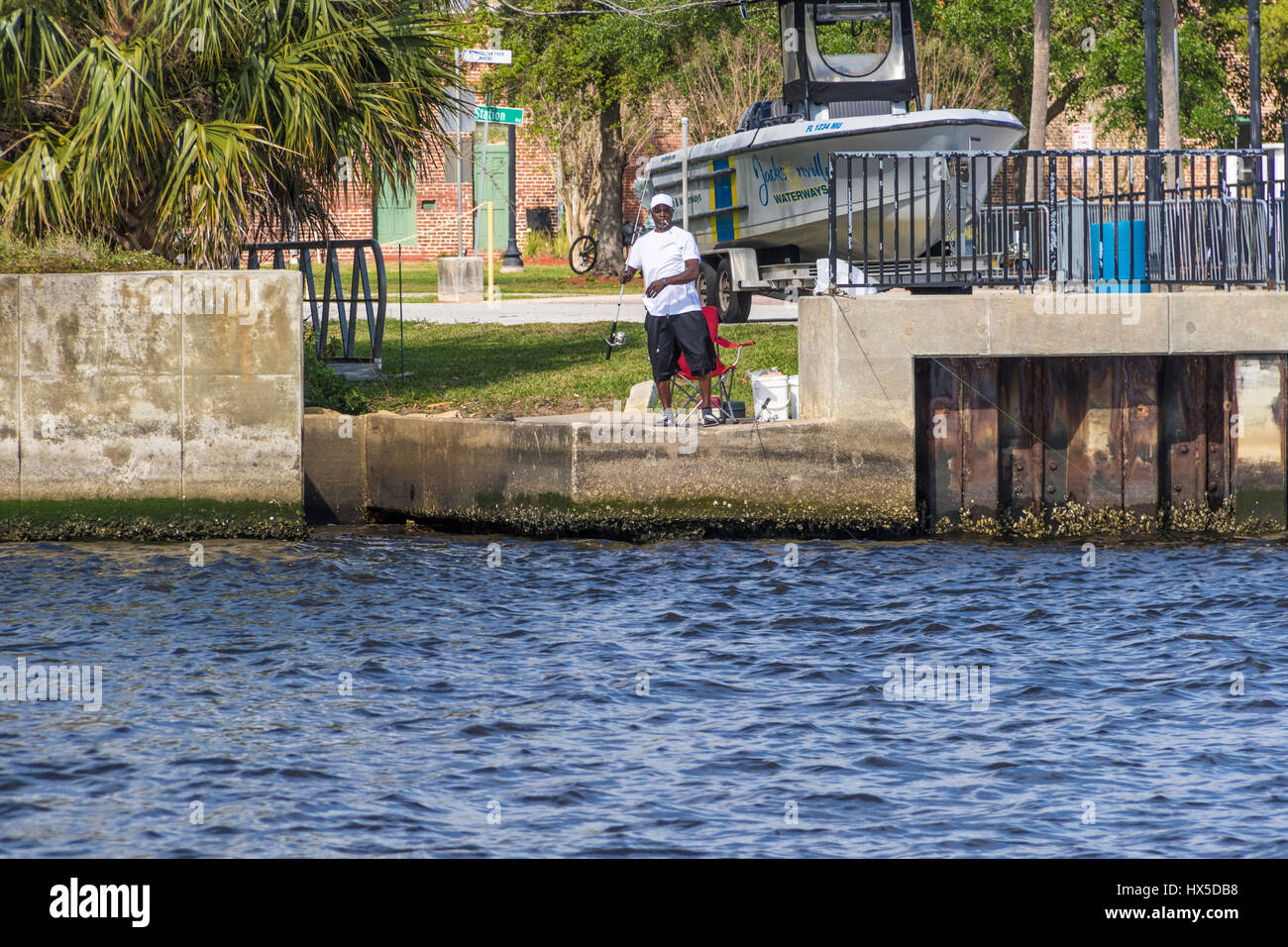 Man fishing in St Johns River in Downtown Jacksonville, FLorida. - Stock Image