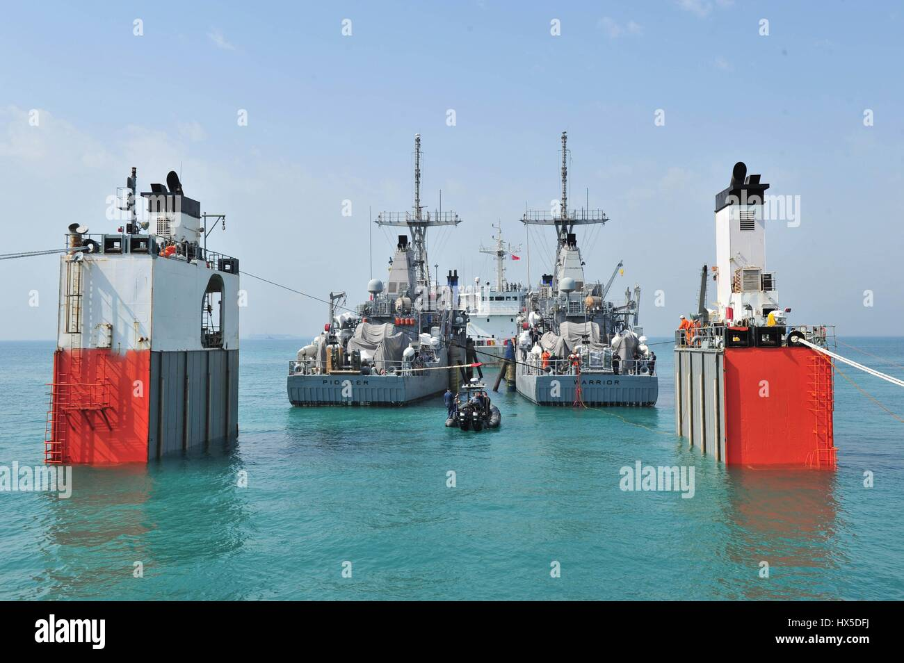 In calm turquoise waters two mine countermeasure ships USS Pioneer and USS Warrior prepare for transport behind Stock Photo