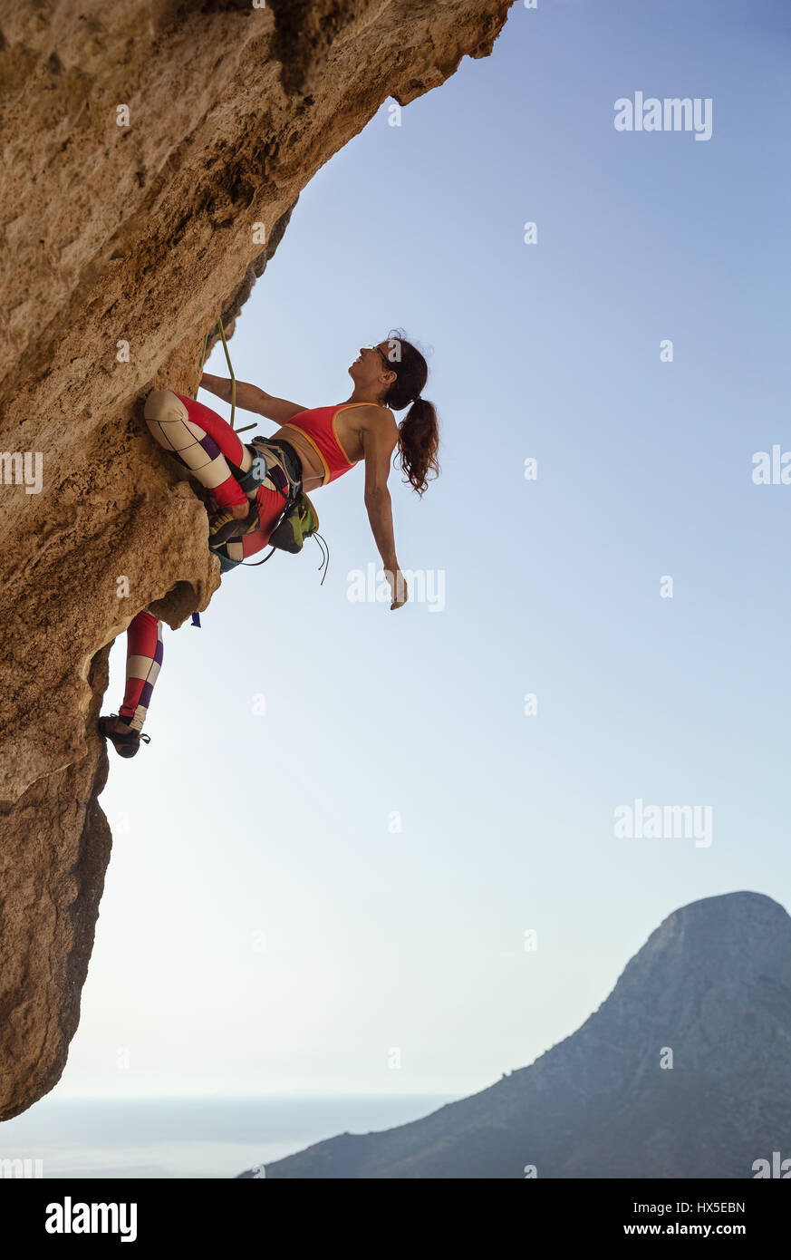 Female rock climber looking up at challenging route on cliff and smiling - Stock Image