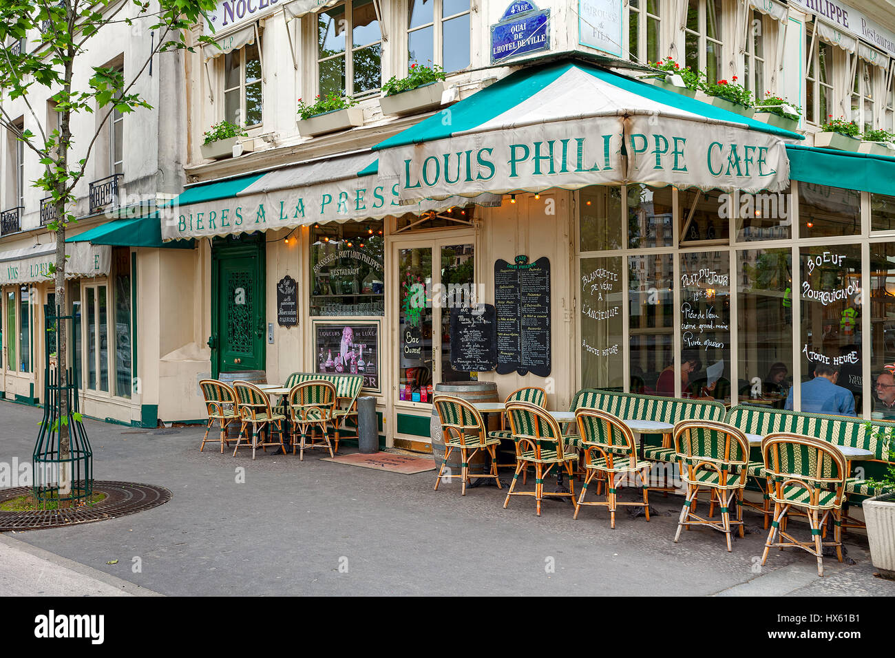 PARIS, FRANCE - MAY 24, 2016: Sidewalk and cafe Louis Philippe - famous parisian bistro since 1851, situated alongside - Stock Image