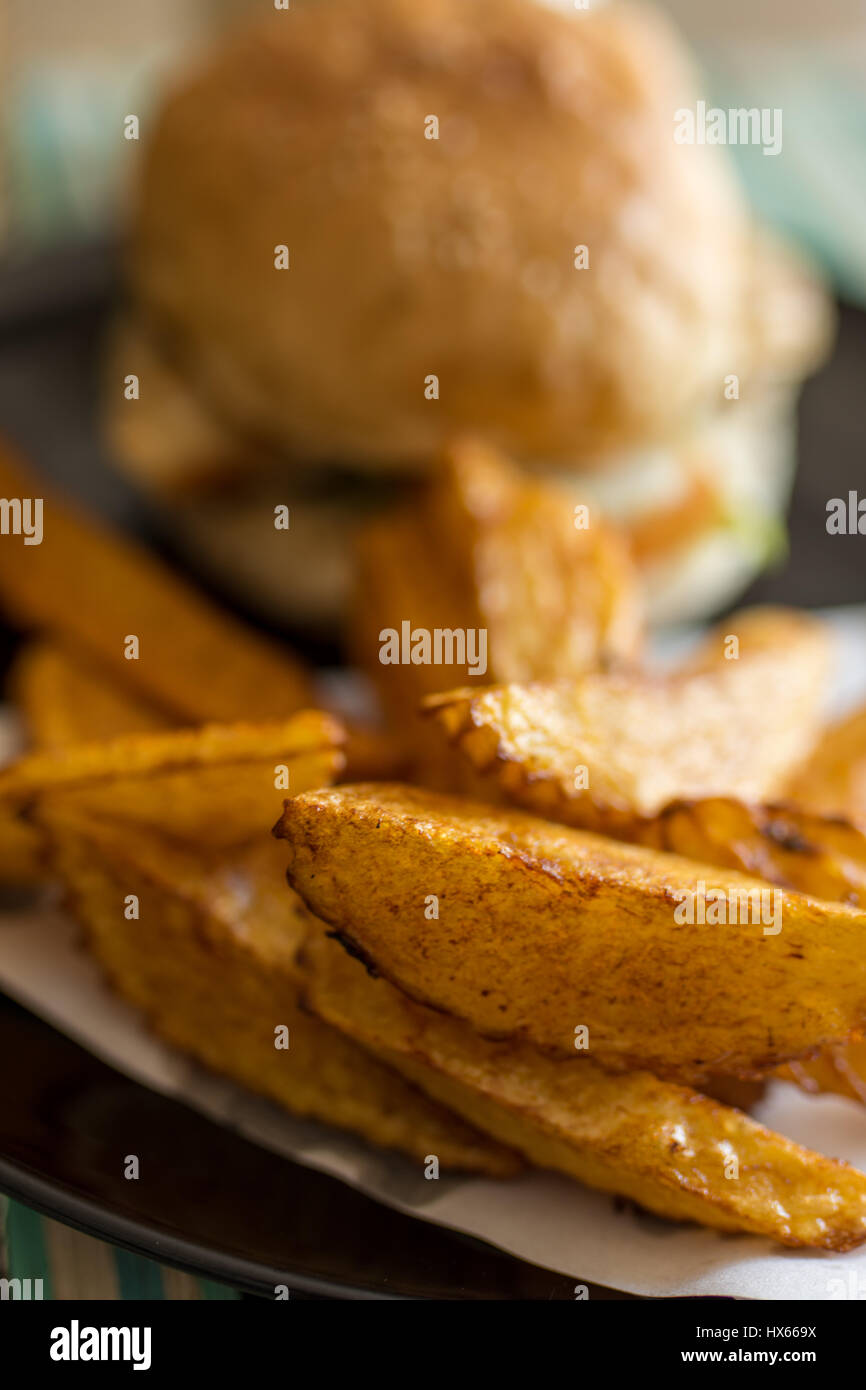 Depth of field photo of burger and hand cut fries on a plate. - Stock Image