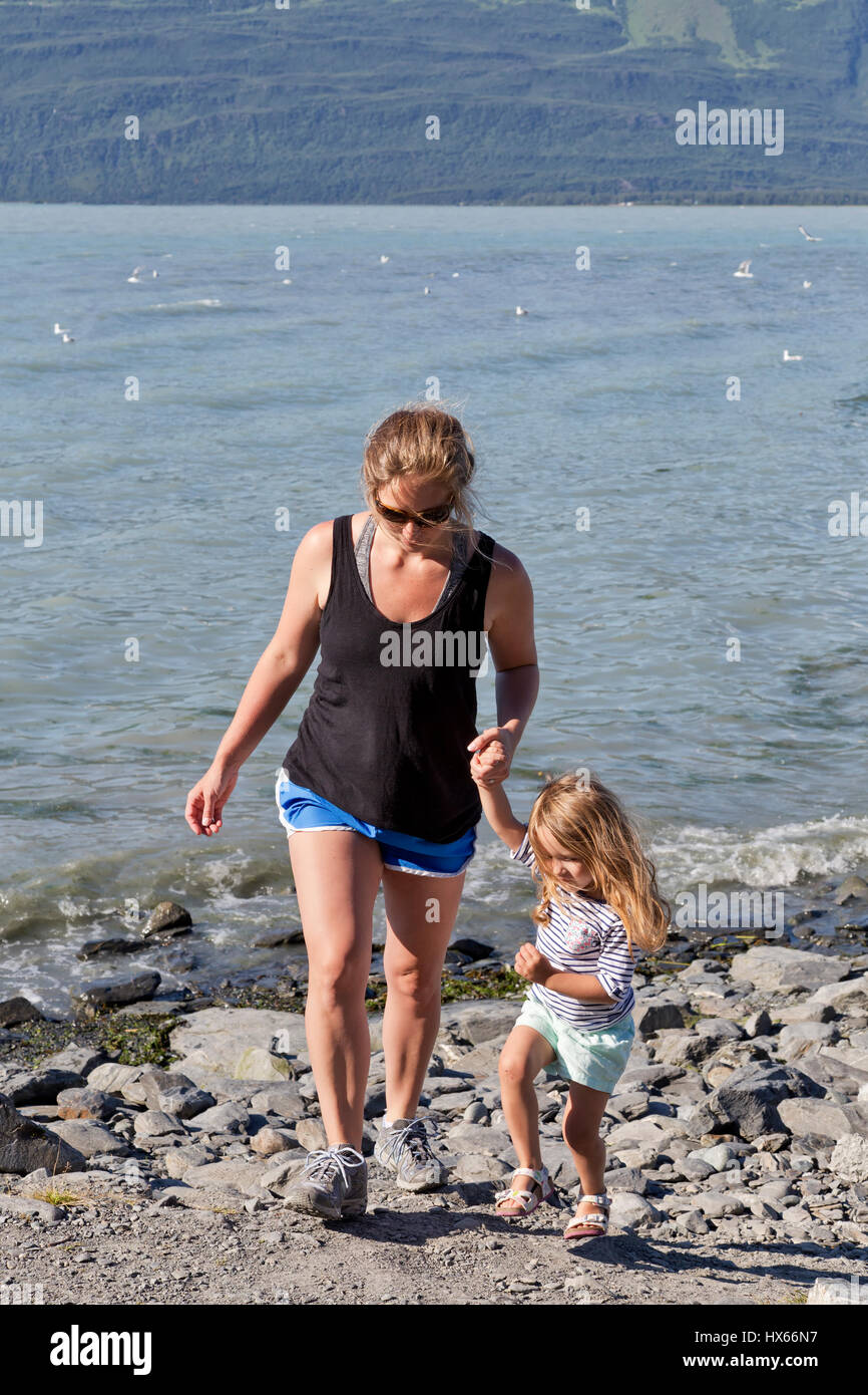 Mother guiding young daughter along Valdez Bay,  uneven ground, early July, pm light, Solomon Gulch Fish Hatchery, - Stock Image