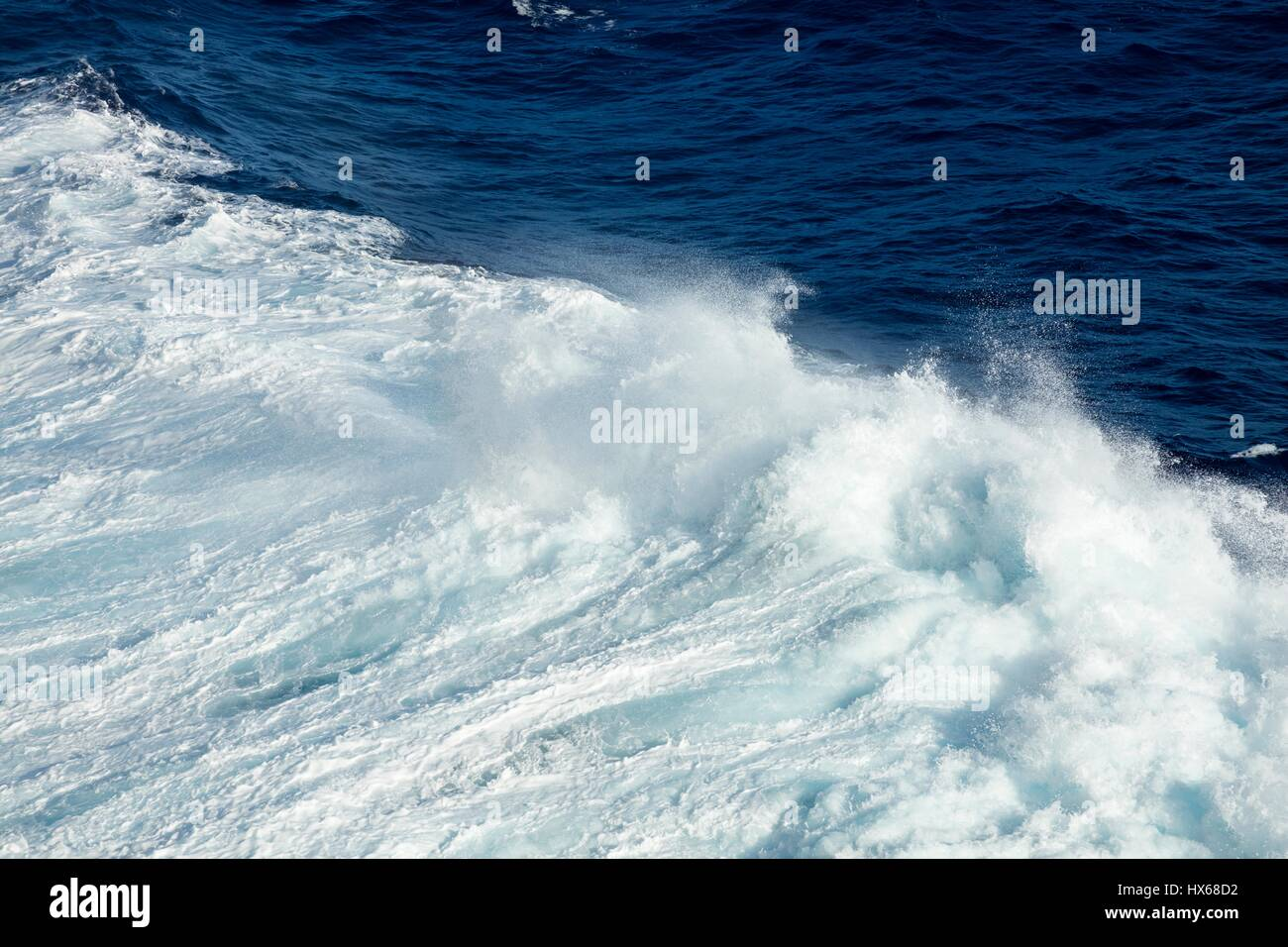 Huge waves and rough seas and sunshine on the open deep ocean - Stock Image
