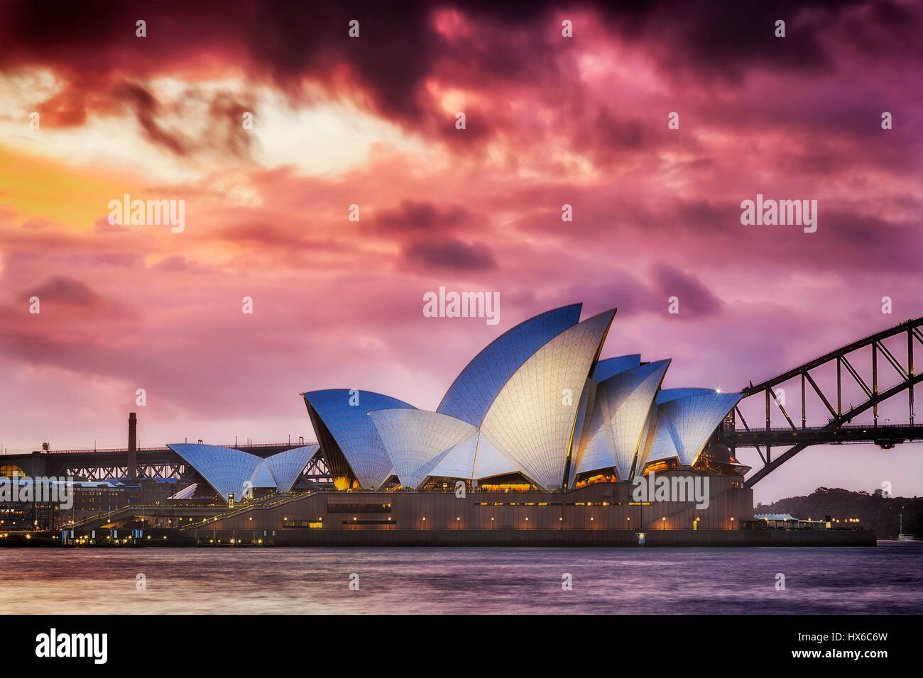Sydney, Australia - 19 March 2017: Magical sunset over world famous landmark - Sydney Opera house and Harbour Bridge. - Stock Image