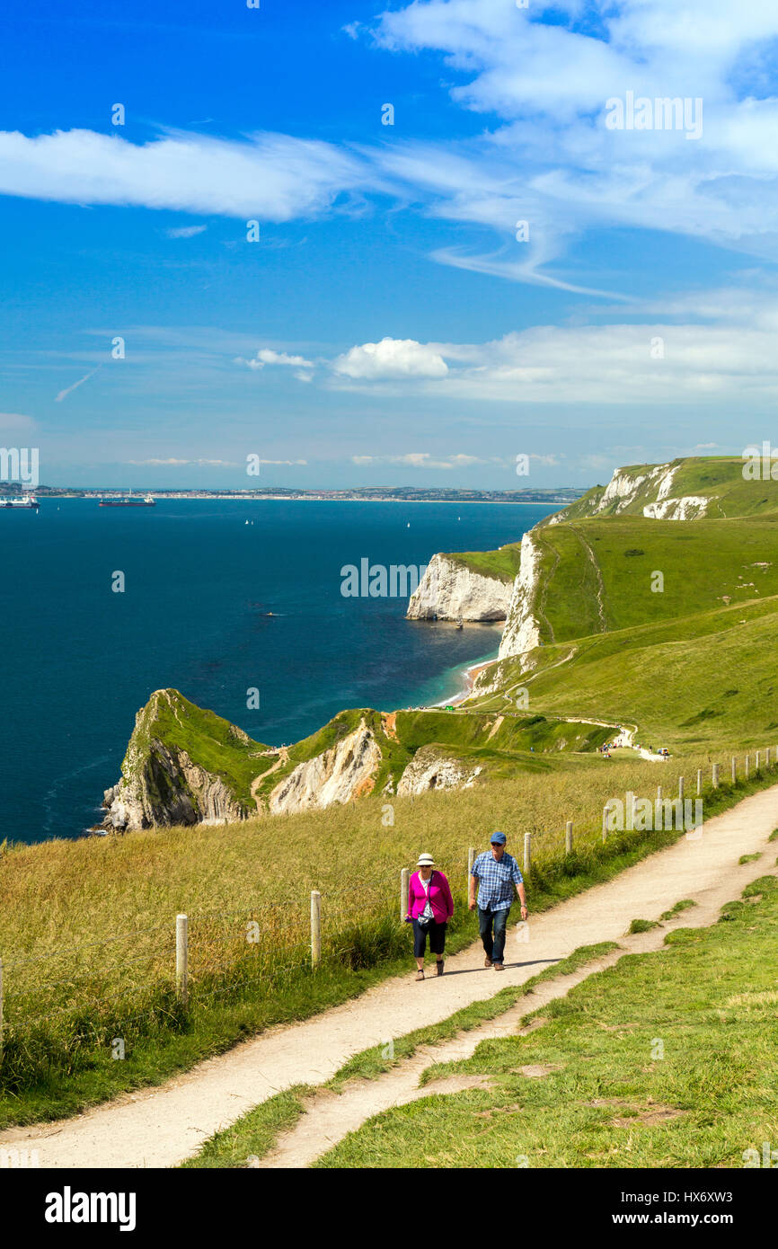 Looking west along the South West Coast Path at walkers near Durdle Door on the Jurassic Coast, Dorset, England - Stock Image