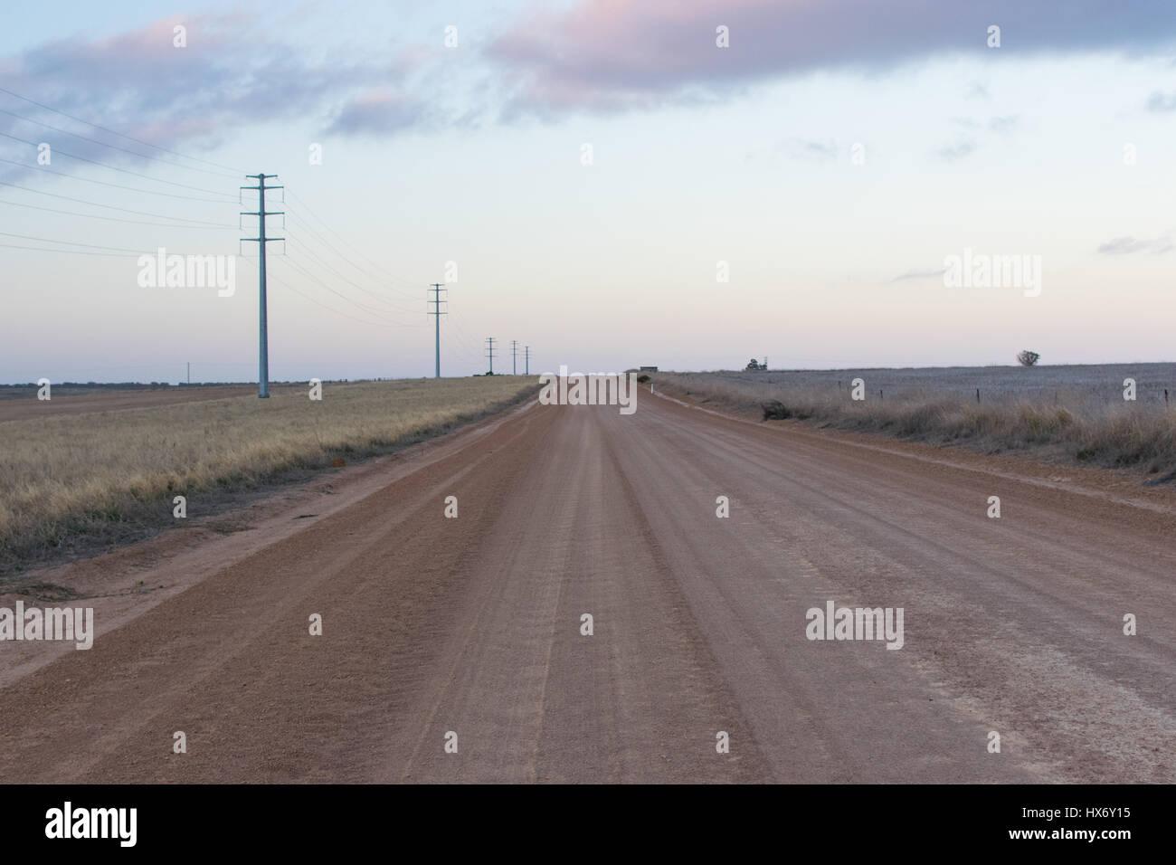 Australian dirt road following power line - Stock Image