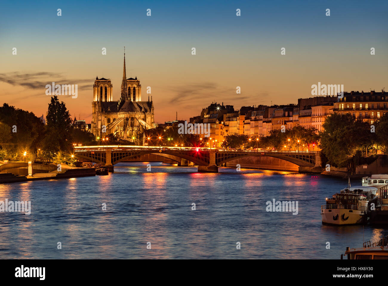 Notre Dame de Paris Cathedral, Seine River and the Ile Saint Louis at twilight. Summer evening with the Sully Bridge - Stock Image