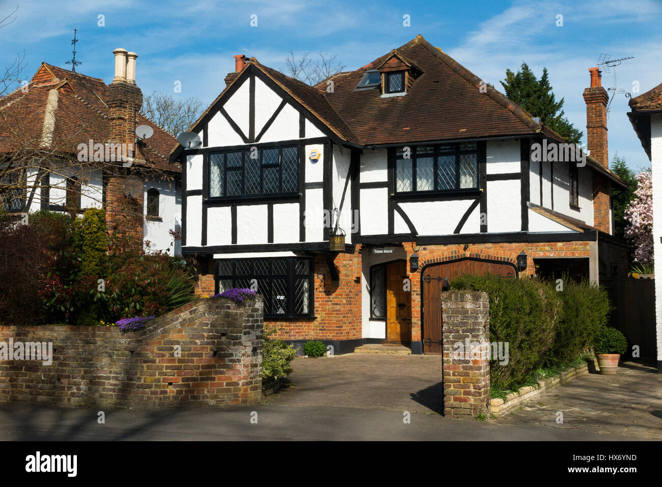 Mock Tudor black and white 1930's house with garage and a drive, in Esher, Surrey. UK. Photograph taken on a - Stock Image