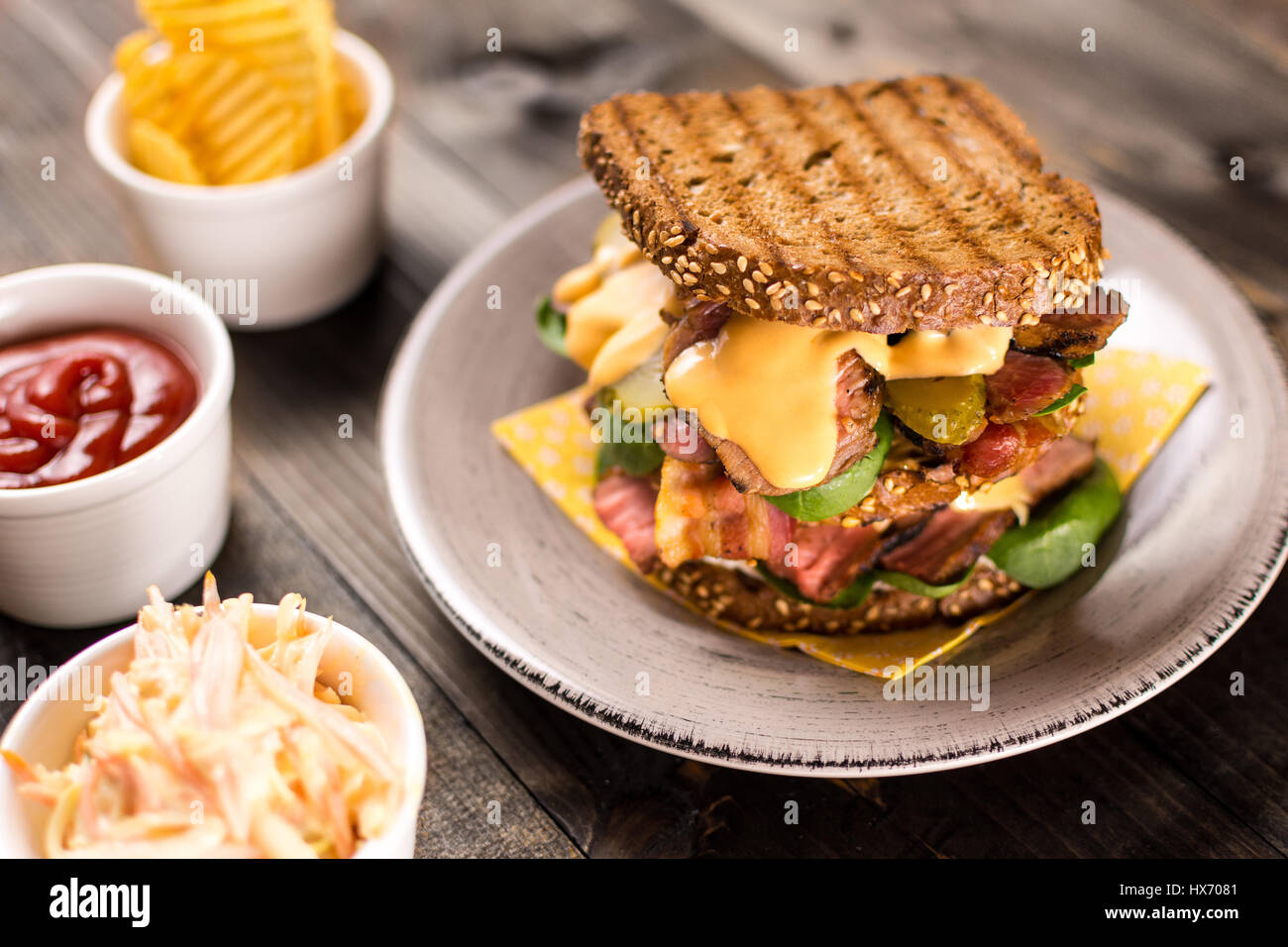 Big Homemade Sandwich with Roast Beef, Bacon, Pickles, Baby Spinach and Coleslaw Dressing in Toasted Bread - Stock Image
