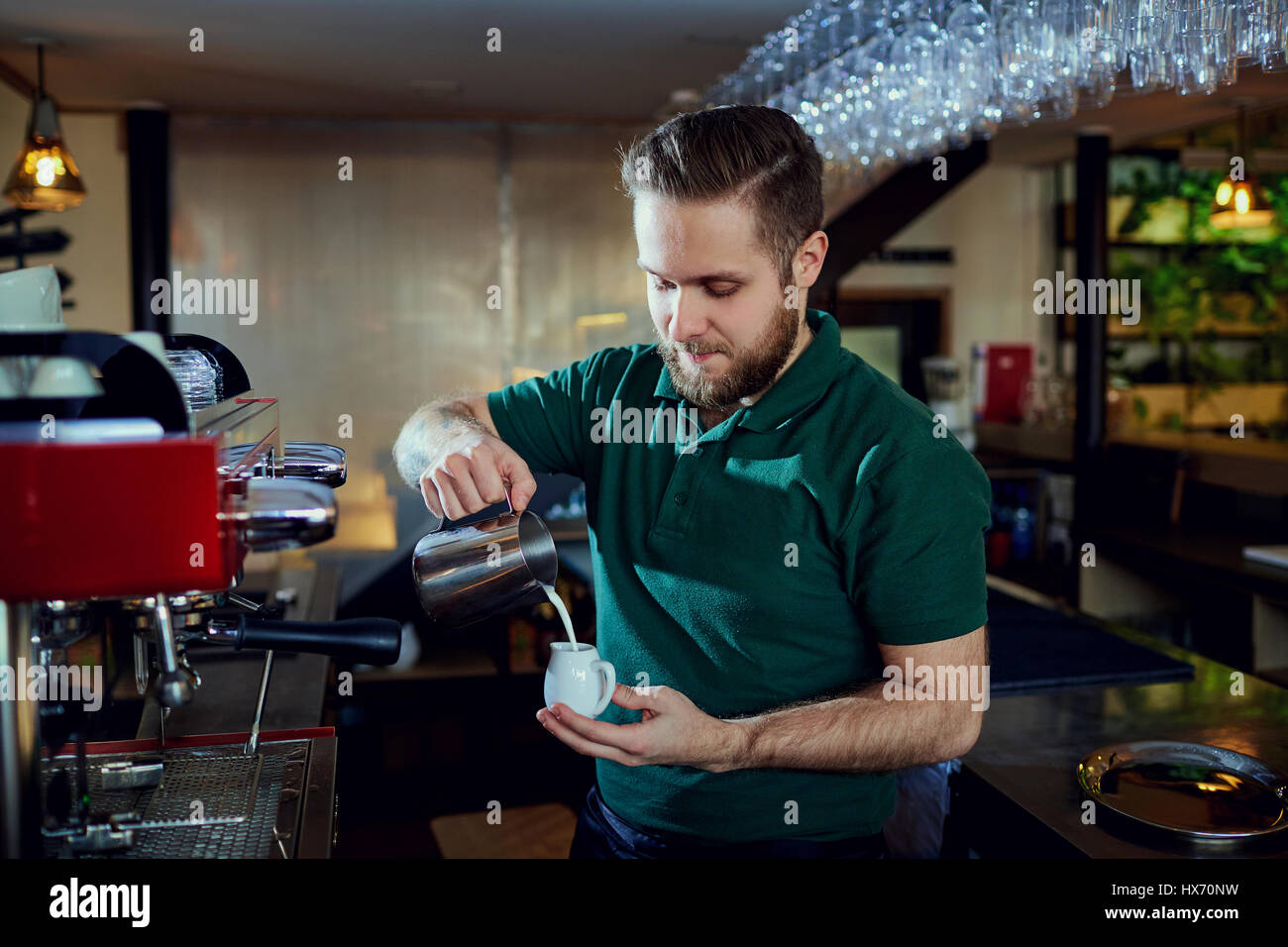 The bartender barista pours  hot milk into a glass in  bar cafe  - Stock Image