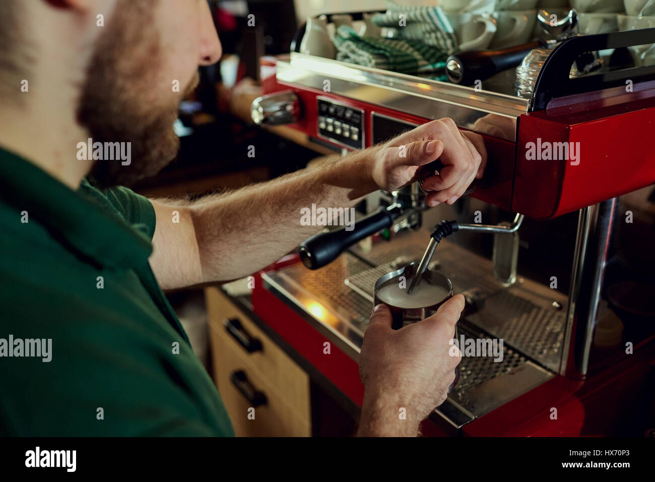 Bartender, barista makes hot milk in a coffee machine behind the - Stock Image