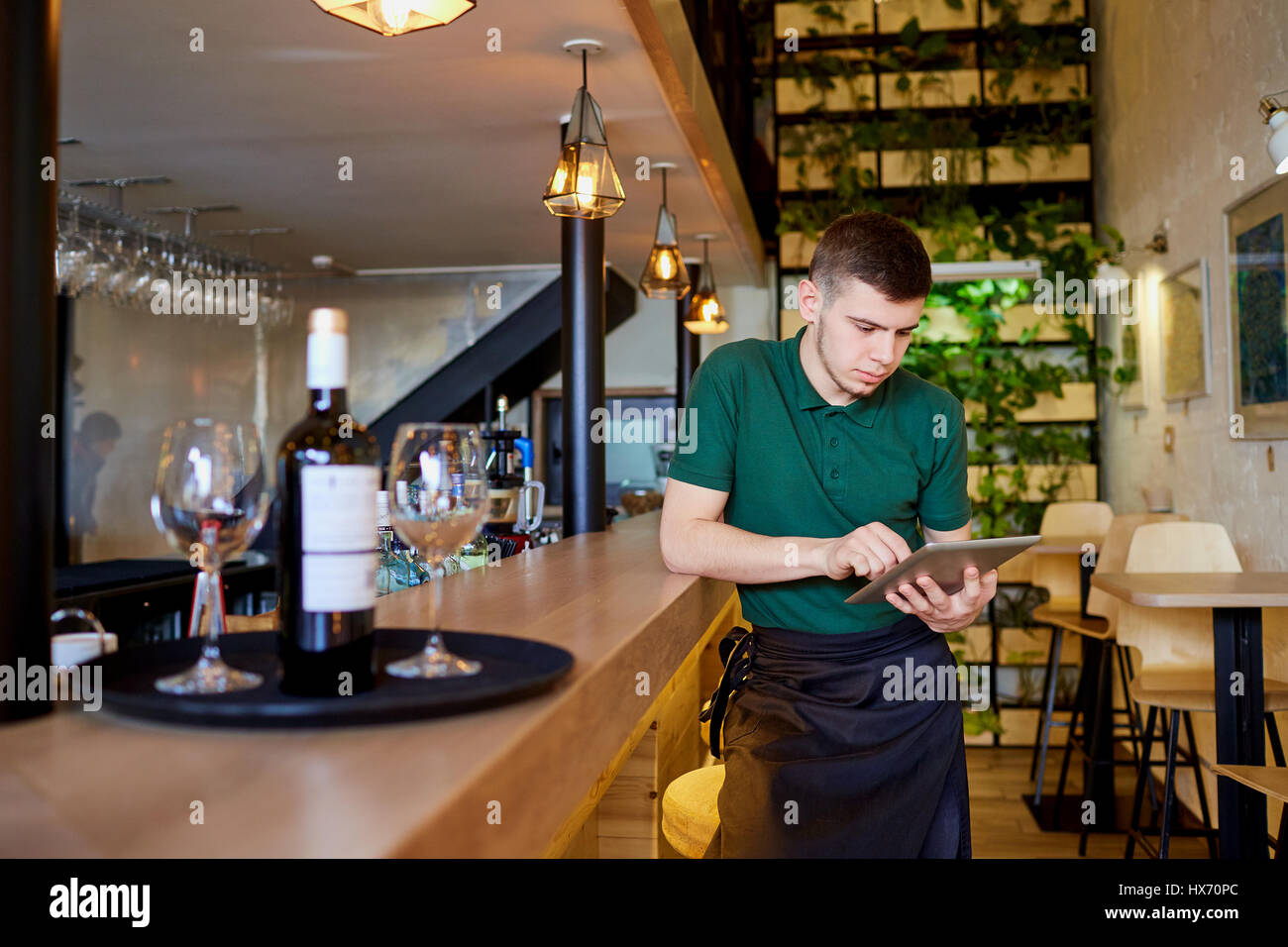 Waiters, bartenders barista rest with the tablet in a break cafe - Stock Image