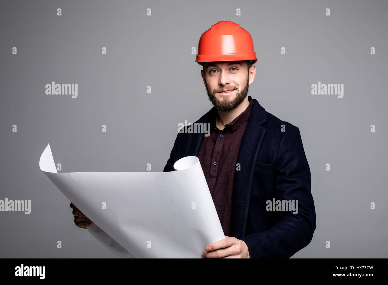 Portrait Of An Architect Builder Studying Layout Plan Of The Rooms, Serious  Civil Engineer Working With Documents On Construction Site