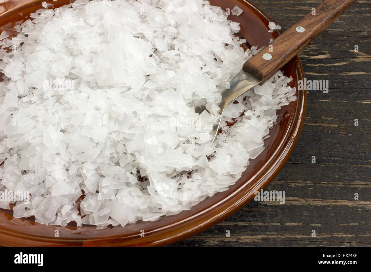 Magnesium chloride flakes, full saucer and spoon - Stock Image