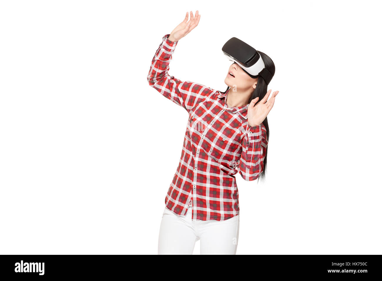 Shocked woman playing game in virtual reality and gesturing. - Stock Image